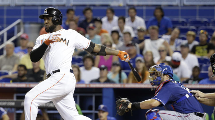 Miami Marlins' Marcell Ozuna, left, watches after hitting a RBI double in the fourth inning as Texas Rangers catcher Geovany Soto, right, looks on during an interleague baseball game, Wednesday, Aug. 20, 2014, in Miami. (AP Photo/Lynne Sladky)