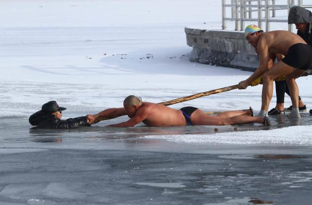 Winter swimmers try to pull man out of icy waters after he was trapped in partially frozen lake at a park in Changchun