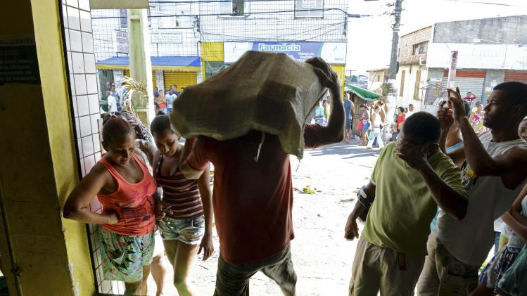 A man carries goods out of a supermarket that was looted during a police strike in Salvador
