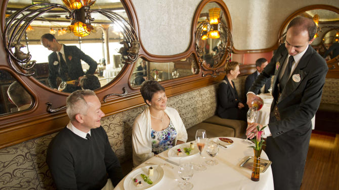 This 2012 photo released by Disney shows a couple enjoying a champagne brunch at Remy, the adults-only restaurant on Disney's Fantasy and Dream ships. The $50 per person brunch  is part of a continuing trend in the cruise ship industry for upscaled and expanded specialty food options, many of which carry extra fees. (AP Photo/Disney, Kent Phillips)