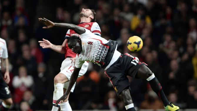 Arsenal's Giroud challenges Liverpool's Sakho during their English Premier League soccer match at the Emirates stadium in London