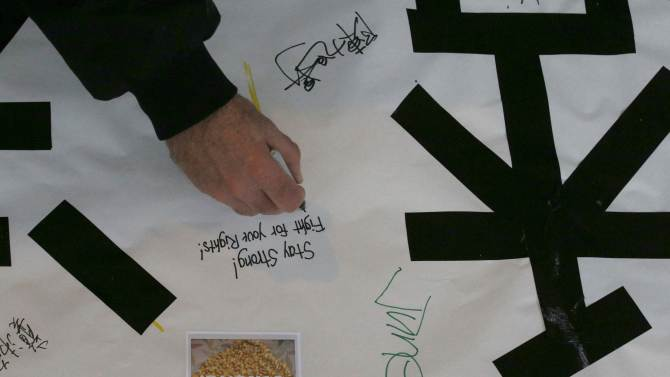 A man writes on a banner at a demonstration in support of the pro-democracy protesters in Hong Kong, in Boston, Massachusetts