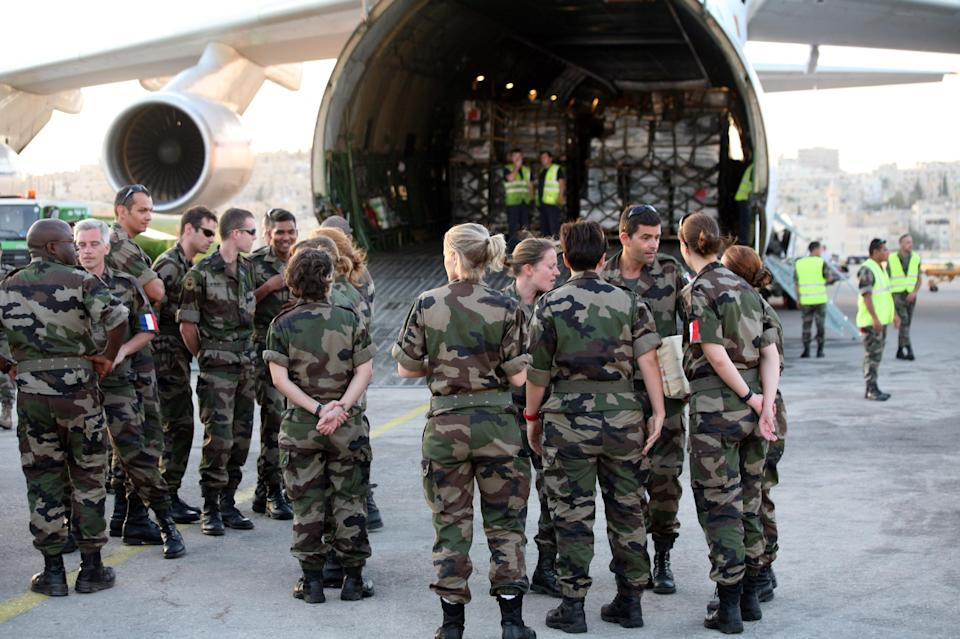 French Military doctors stand in front the cargo plane with medical supplies  at Marka airport,  in Amman, Jordan, Saturday, Aug. 11, 2012. The French military will open a field hospital at a Syrian refugees camp at the Jordanian -Syrian border.  (AP photo/Mohammad Hannon)