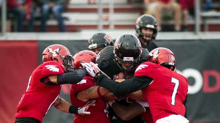 Montana Western running back Sam Rutherford is tackled by, left to right, Eastern Washington's Jake Hoffman, Todd Raynes, Tevin McDonald (7) during the first half of an NCAA college football game, Saturday, Aug. 30, 2014, in Cheney, Wash. (AP Photo/The Spokesman-Review, Colin Mulvany)
