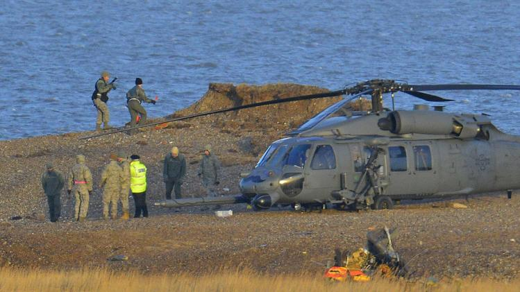 A Pave Hawk helicopter, military personnel and emergency services attend the scene of a helicopter crash on the coast near the village of Cley in Norfolk, eastern England