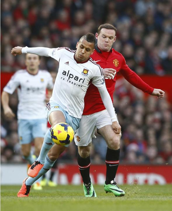 Manchester United's Rooney challenges West Ham's Morrison during their English Premier League soccer match at Old Trafford