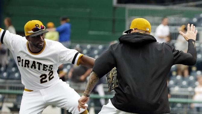 Pittsburgh Pirates' Andrew McCutchen, left, celebrates with A.J. Burnett after closing out a 5-2 win over the Milwaukee Brewers in a baseball game in Pittsburgh, Sunday, April 19, 2015. (AP Photo/Gene J. Puskar)