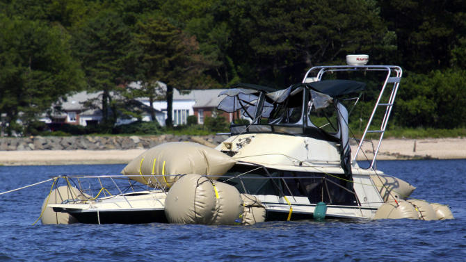 FILE - This July 11, 2012 file photo shows the Kandi Won being towed to shore after being raised from the bottom of Oyster Bay, in Oyster Bay, N.Y. The yacht capsized and sank, killing three children in its cabin, after a July Fourth outing to watch fireworks. A New York prosecutor said in a report released Wednesday, July 3, 2013, 34-foot yacht that capsized because it was overcrowded. (AP Photo/Howard Schnapp, File)