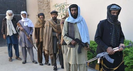 Former Taliban fighters wait to hand over their weapons as they join a government peace and reconciliation process, at a ceremony in Jalalabad, capital of Nangarhar province, on November 20, 2013