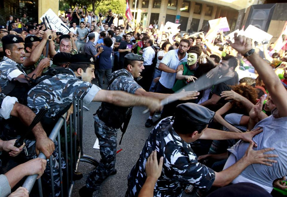 Lebanese riot police beat up civil society protesters near the Parliament in Beirut, Lebanon, Thursday, June 20, 2013. Lebanon's parliament on May 29 extended its term by a year and a half, skipping scheduled elections because of the country's deteriorating security linked to the civil war next door in Syria. (AP Photo/Bilal Hussein)