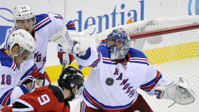 New York Rangers goaltender Henrik Lundqvist, right, of Sweden, makes a save as New Jersey Devils' Martin Havlat (9), Rangers' Marc Staal (18) and Chris Mueller (14) look on during the second period of an NHL hockey game Tuesday, Oct. 21, 2014, in Newark, N.J. The Rangers won 4-3 in overtime. (AP Photo/Bill Kostroun)