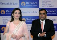 Reliance Industries chairman Mukesh Ambani (right) arrives for the company&#39;s annual general meeting with his wife Nita in Mumbai on Thursday. Reliance says it will invest $18 bn over the next four to five years to expand in the country and more than double operating profit