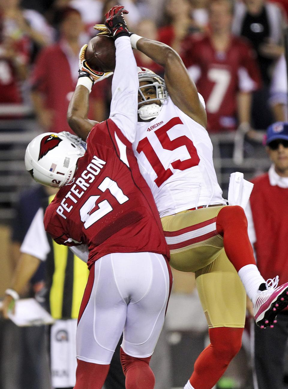 San Francisco 49ers wide receiver Michael Crabtree (15) pulls in a touchdown pass as Arizona Cardinals cornerback Patrick Peterson (21) defends during the first half of an NFL football game, Monday, Oct. 29, 2012, in Glendale, Ariz. (AP Photo/Paul Connors)