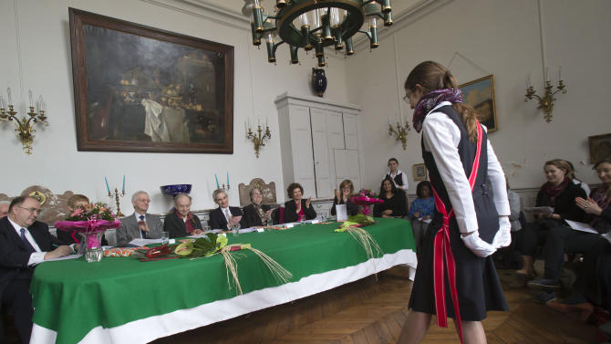 """In this photo taken Friday, March 22, 2013, jury member Michael Edwards, third from left, listens to a contestant during the 21st annual poetry recitation competition at the Maison d'Education de la Legion d'Honneur in Saint Denis, north of Paris. The man who will soon become the newest official guardian of the French language has spoken: English, he says, is jumping the barricades and threatening the language of Moliere. Edwards should know. He's British - the first to become one of the 40 esteemed """"immortals"""" of the Academie Francaise, the institution that has watched over the French language since 1635. (AP Photo/Michel Euler)"""