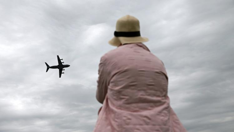 An aviation enthusiast watches an Airbus A400M aircraft performing during The Royal International Air Tattoo at RAF in Fairford