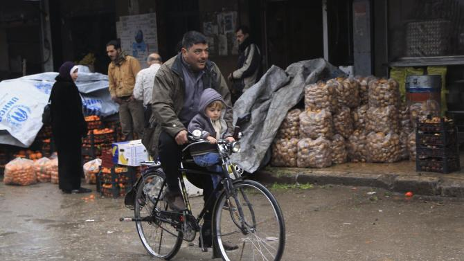 A man and a child ride a bicycle past past produce vendors in the old city of Aleppo