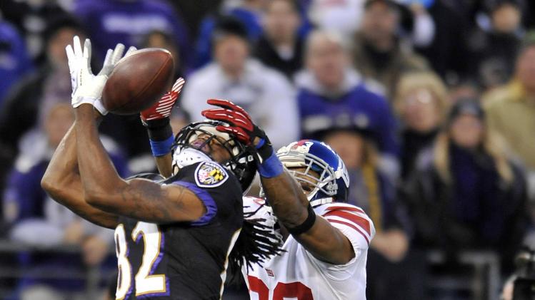 Baltimore Ravens wide receiver Torrey Smith, left, completes a 43-yard pass as he is pressured by New York Giants cornerback Corey Webster in the first half of an NFL football game in Baltimore, Sunday, Dec. 23, 2012. (AP Photo/Gail Burton)