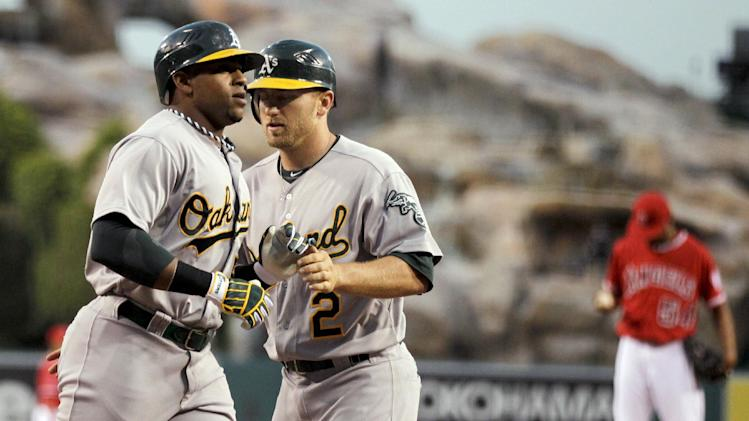 Oakland Athletics' Yoenis Cespedes, left, celebrates his three-run home run with Cliff Pennington off Los Angeles Angels starting pitcher Ervin Santana during the first inning of a baseball game in Anaheim, Calif., Wednesday, April 18, 2012. (AP Photo/Chris Carlson)
