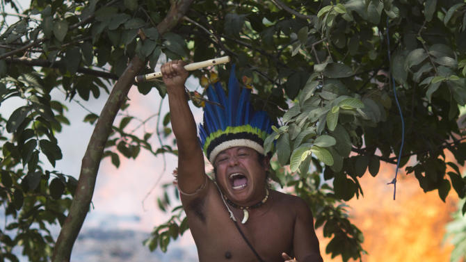 An indigenous man shouts to police, clutching a flute from inside the old Indian Museum where a fire burns behind in Rio de Janeiro, Friday, March 22, 2013. Police in riot gear invaded an old Indian museum complex Friday and pulled out a few dozen indigenous people who for months resisted eviction from the building, which will be razed as part of World Cup preparations next to the legendary Maracana football stadium. (AP Photo/Felipe Dana)