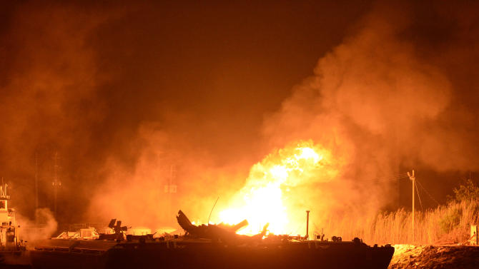 A massive explosion at 3a.m. EDT on one of the two barges still ablaze in the Mobile River in Mobile, Ala., on Thursday, April 25, 2013. Three people were injured in the blast. Fire officials have pulled units back from fighting the fire due to the explosions and no immediate threat to lives. (AP Photo John David Mercer)
