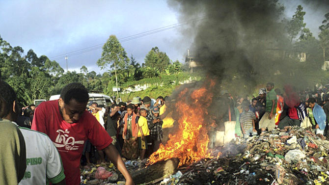 In this Feb. 6, 2013 file photo, hundreds of bystanders watch Helen Rumbali, a woman accused of witchcraft, being burned alive in the Western Highlands provincial capital of Mount Hagen in Papua New Guinea. There is no clear explanation for the apparent uptick in killings in parts of the South Pacific nation, and even government officials seem at a loss to say why this is happening. Some are arguing the recent violence is fueled not by the nation's widespread belief in black magic but instead by economic jealousy born of a mining boom that has widened the country's economic divide and pitted the haves against the have-nots. (AP Photo/Post Courier, File) PAPUA NEW GUINEA OUT