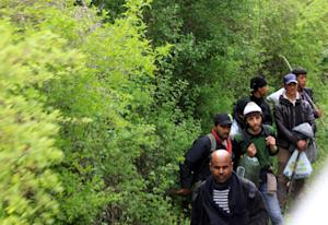 A group of migrants walk near to the railroad tracks …