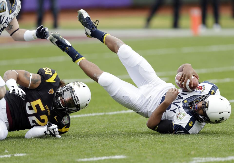 Navy quarterback Keenan Reynolds, right, is sacked by Arizona State linebacker Carl Bradford (52) during the first half of the Fight Hunger Bowl NCAA college football game in San Francisco, Saturday, Dec. 29, 2012. (AP Photo/Marcio Jose Sanchez)