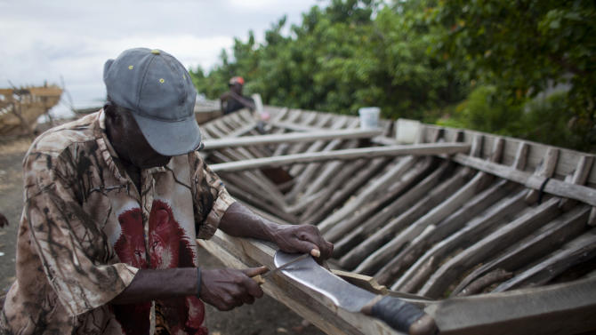 In this May 4, 2013 photo, a boat maker sharpens his machete which he will use to build a sailboat in Leogane, Haiti. The 30-foot-long boats, whose frames resemble the rib cage of a small dinosaur, are purchased by smugglers for around $12,000 and then taken to northern Haiti to find passengers. One boat builder said he has four or five regular customers. (AP Photo/Dieu Nalio Chery)