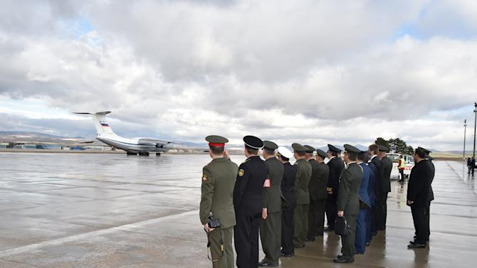 Russian and Turkish army officials salute the Russian aircraft as it advances on the tarmac of Esenboga Airport