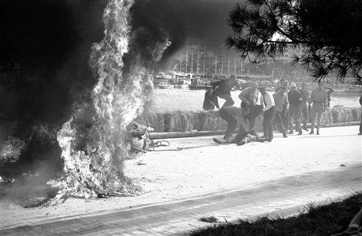 Italian race driver Lorenzo Bandini sprawls on a ground after being pulled from his flaming Ferrari during Grand Prix Race in Monaco May 7, 1967. He was taken a hospital. His car hit straw bales on 82nd lap, flipped over, and burst into flames. He has burns over 65 per cent of his body. (AP Photo)