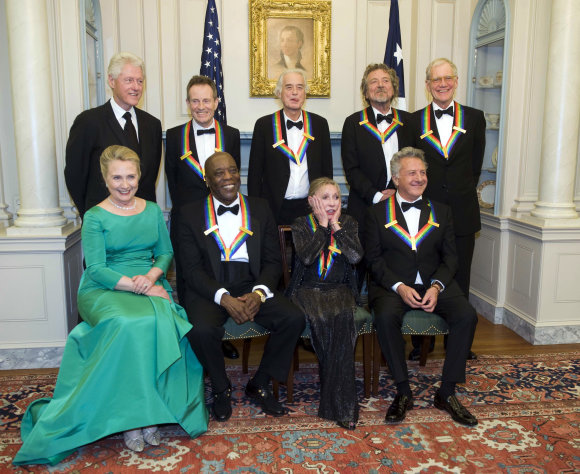 2012 Kennedy Center Honoree Natalia Makarova, front row, second right, reacts to all the photos being taken during a group photo after the State Department Dinner for the Kennedy Center Honors gala Saturday, Dec. 1, 2012 at the State Department in Washington. From left are former President Bill Clinton, Secretary of State Hillary Rodham Clinton, John Paul Johns, Buddy Guy, Jimmy Page, Makarova, Robert Plant, Dustin Hoffman and David Letterman. (AP Photo/Kevin Wolf)