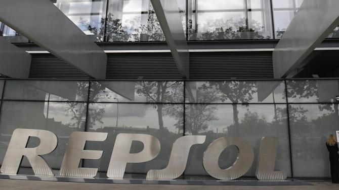 A woman stands beside the logo of Spanish oil company Repsol outside its headquarters in Madrid