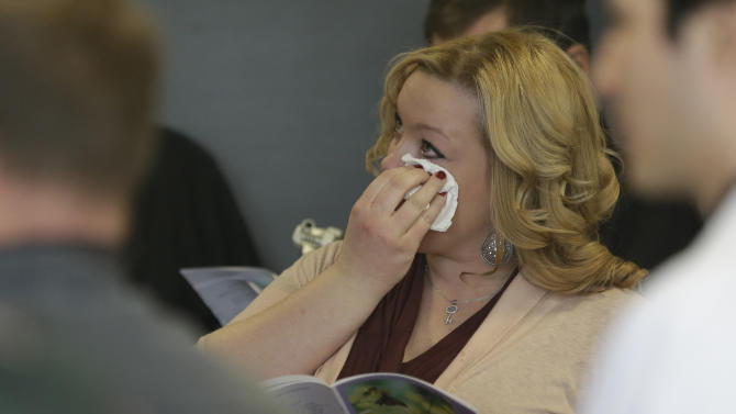 In this photo taken Friday, Jan. 25, 2013, in Gary, Ind., Linsdey Ellingsen, granddaughter of donor William N. Kelly, wipes a tear from her eye as a song is sung during a memorial service for bodies donated to science at Indiana University School of Medicine - Northwest. During the hour long service, relatives of donors gather around the steel tables where their loved ones were dissected along with the medical students who worked on the bodies during the previous semester. The students read letters of appreciation, clergy offer prayers, and tears are shed. The program is geared towards teaching the medical students that this is not merely a cadaver, but a person, and their first patient. (AP Photo/M. Spencer Green)