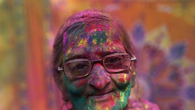 Widow daubed in colours takes part in Holi celebrations organised by non-governmental organisation Sulabh International at a widows' ashram at Vrindavan