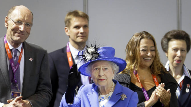 Britain's Queen Elizabeth II waves to spectators inside the Aquatics center, in the Olympic Park at the 2012 Summer Olympics, Saturday, July 28, 2012, in London. (AP Photo/Ben Curtis)