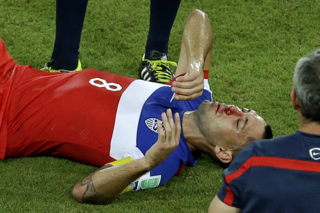 United States' Clint Dempsey lies on the pitch after being kicked in his face during the group G World Cup soccer match between Ghana and the United S...