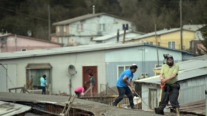 People clean their houses and streets, covered in ash from the Calbuco volcano, in La Ensenada, southern Chile, on April 25, 2015