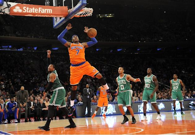 New York Knicks' Carmelo Anthony (7) dunks a basket as Boston Celtics' Jared Sullinger (7), Avery Bradley (0), Brandon Bass (30) and Jordan Crawford (27) watch from behind during the first hal