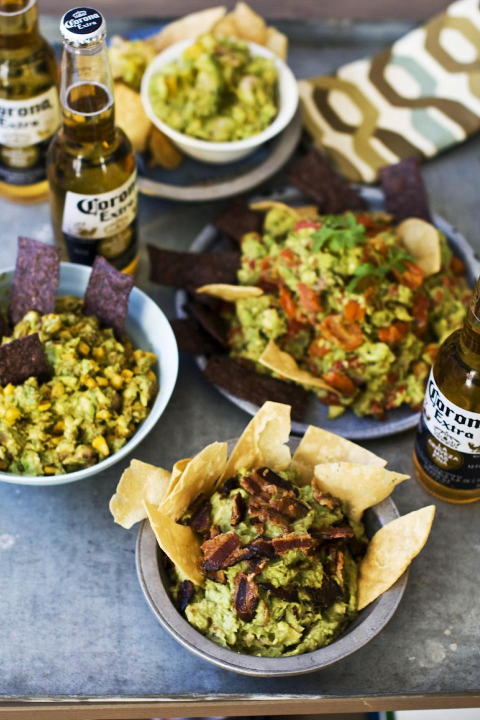 In this image taken on January 7, 2013, sweet heat bacon guacamole, front, chipotle corn guacamole, middle left, shrimp and mango guacamole, top, and roasted fresh salsa guacamole, middle right, are shown served in bowls in Concord, N.H.  (AP Photo/Matthew Mead)