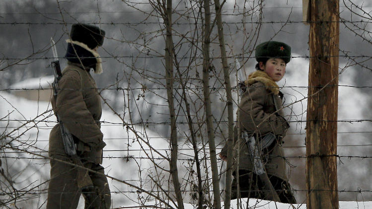 A North Korean female soldier, right, looks back as she and another patrol on a pathway along the bank of the Yalu River, the China-North Korea border river, near North Korea's town of Sinuiju, opposite to the Chinese border city of Dandong, Sunday Nov. 28, 2010. (AP Photo/Andy Wong)