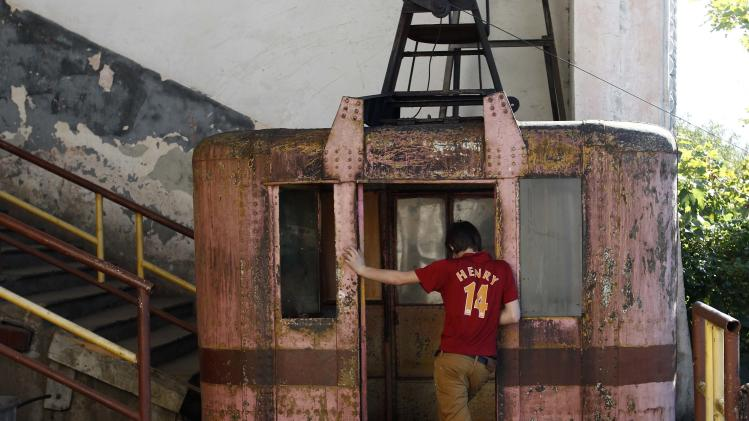 A boy stands at the door of a 60-year-old cable car in the town of Chiatura