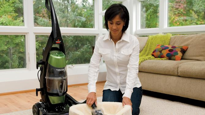 This undated photo provided by BISSELL shows a woman using a BISSELL Total Floors Pet Vacuum that features a crevice tool port to suction pet hair away from walls where it accumulates without reaching or bending. Uses Febreze filter for odors. A holiday present for Fido or Fluffy used to be an extra table scrap or a new squeeze toy. But as with gifts for their human counterparts, pet presents are becoming increasingly high-tech. (AP Photo/BISSELL)