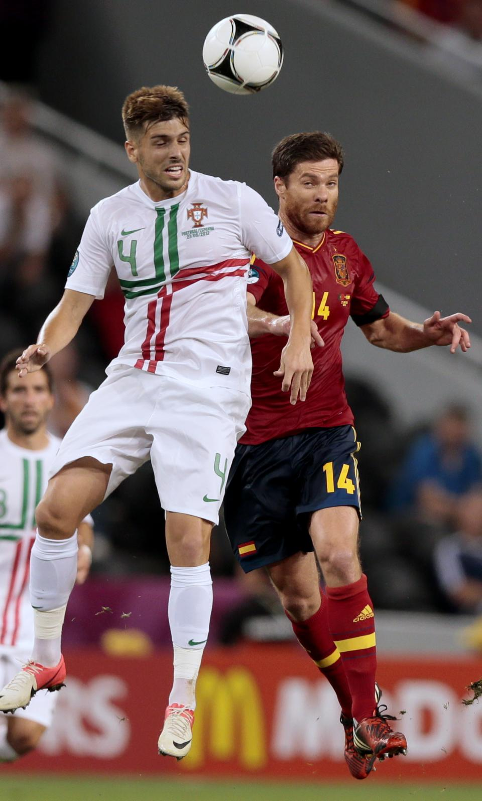 Portugal's Miguel Veloso, left, and Spain's Xabi Alonso go for a header during the Euro 2012 soccer championship semifinal match between Spain and Portugal in Donetsk, Ukraine, Wednesday, June 27, 2012. (AP Photo/Ivan Sekretarev)