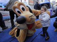 "Two-year-old Adisen Lee, from New York, meets Disney character Pluto in New York's Times Square, Wednesday, Oct. 17, 2012. On Wednesday, Disney announced a new program for 2013, ""Limited Time Magic,"" in which guests will encounter surprise weekly themes at Disney parks in Florida and California. The program was described as ""52 weeks of magical experiences big and small that appear, then disappear as the next special surprise debuts."" For example, a weeklong Valentine's Day celebration might include pink lighting on Disney castles, surprise meet-and-greets with Disney characters and candlelit dinners for lovebirds. (AP Photo/Richard Drew)"