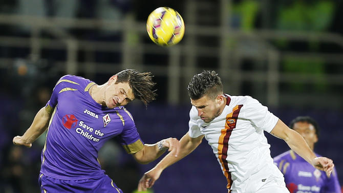 Fiorentina forward Mario Gomez, left, and Roma midfielder Kevin Strootman jump for the ball during a serie A soccer match between Fiorentina and Roma in Florence, Italy, Sunday, Jan. 25, 2015. (AP Photo/Fabio Muzzi )
