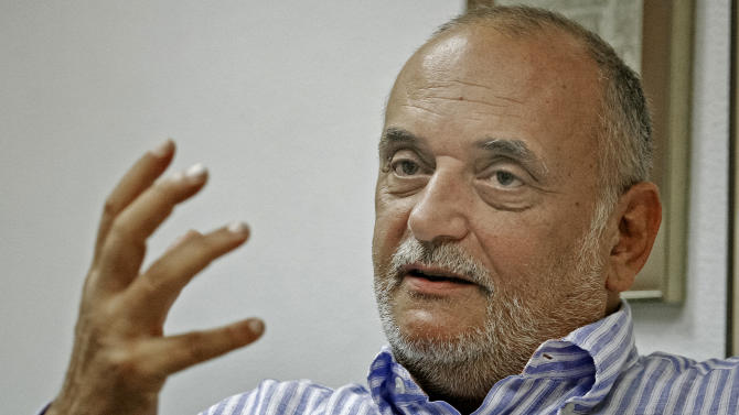 File - In a Sept. 6, 2007 file picture Romanian oil tycoon Dinu Patriciu, gestures during an interview with the Associated Press, in Bucharest Romania. Dinu Patriciu, an emblematic politician from Romania's early post-communist years whose later career as an oil tycoon was marred by legal troubles, died Tuesday, Aug. 19, 2014, at the age of 64, in a London hospital, said former Prime Minister Petre Roman.(AP Photo/Marius Nemes, File)