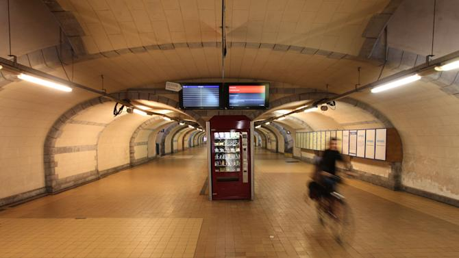 A woman cycles through a deserted hall of the main train station in Ghent, western Belgium, Wednesday, Oct. 3, 2012. A 24-hour strike by Belgian rail workers on Wednesday paralyzed train traffic throughout Belgium and the international high-speed service to London and Paris. The strike, which started late Tuesday, reached its peak during the Wednesday morning rush hour when tens of thousands of commuters had to take to traffic-choked highways to get into the capital or work. (AP Photo/Yves Logghe)