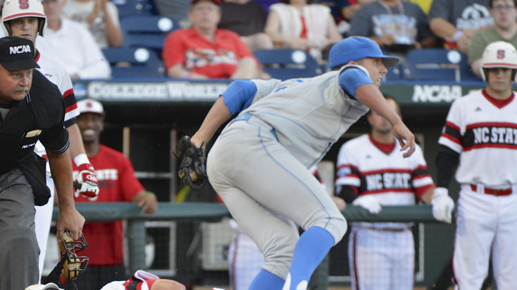 UCLA pitcher Nick Vander Tuig steps over North Carolina State's Jake Armstrong after tagging him out at home plate on a single by Trea Turner in the third inning of an NCAA College World Series game in Omaha, Neb., Tuesday, June 18, 2013. (AP Photo/Ted Kirk)