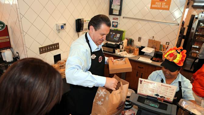 This Nov. 22, 2012 photo provided by Boston Market shows Boston Market CEO George Michel, center, working inside a company's Miami-area restaurant on the home style restaurant chains busiest day of the year, Thanksgiving, in Miami. Boston Market Corp. is reporting record Thanksgiving sales this year, and it's already planning for next Thanksgiving.The Golden, Colo.-based restaurant chain had not yet released specific dollar figures but said total sales per restaurant from Nov. 19 to Nov. 23 were up 13 percent from a comparable period last year. (AP Photo/Boston Market, Marc Serota)