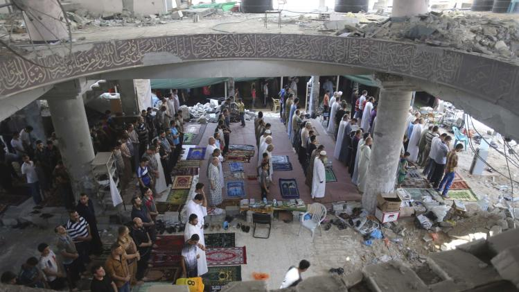 Palestinians perform Friday prayers at the remains of a mosque in Gaza City